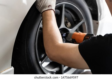 Cropped image of profession mechanic repairing car's tire in automobile shop