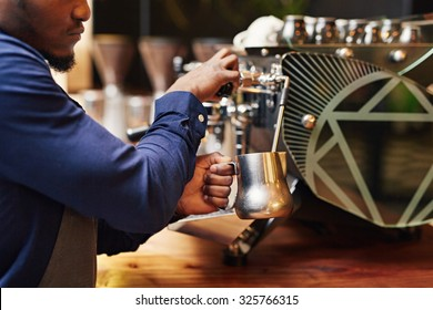 Cropped image of a professional barista steaming milk on a coffee machine with skill