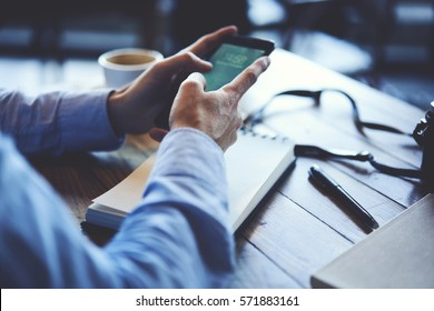 Cropped image of prosperous man holding smartphone using application to booking suite in luxury hotel for business trip using wireless connection to internet resting in cafe interior drinking coffee
