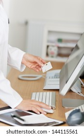 Cropped image of receptionist holding ID card while using computer at reception counter in dentist's clinic