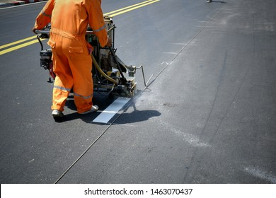 Cropped image of road worker using thermoplastic spray road marking machine to painting white line on asphalt street in the city