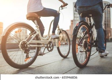 Cropped image of romantic couple in the city with bicycles. Cycling and enjoying the company of each other.