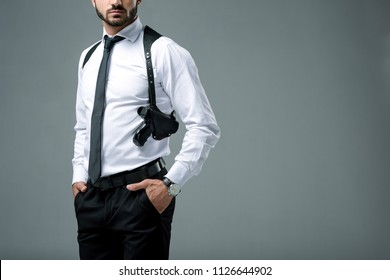 cropped image of security guard standing with gun isolated on grey