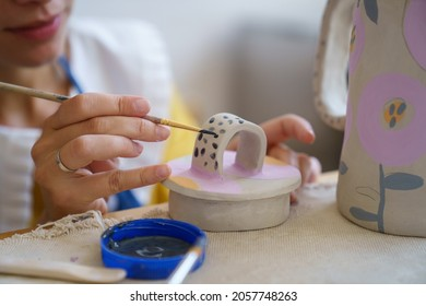 Cropped image of self employed ceramist craftswoman drawing decoration on ceramic cup for clay jug during master class in pottery studio. Creative occupation in workshop. Relax with handicraft concept