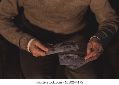 cropped image of senior man holding old photos at home