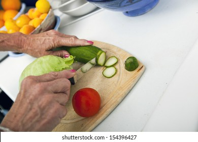 Cropped image of senior woman cutting vegetables on chopping board in kitchen