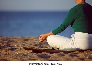 Cropped image of senior woman in meditation on sandy beach. Elderly woman sitting on the beach in lotus pose doing relaxation exercise . Mature woman doing yoga
