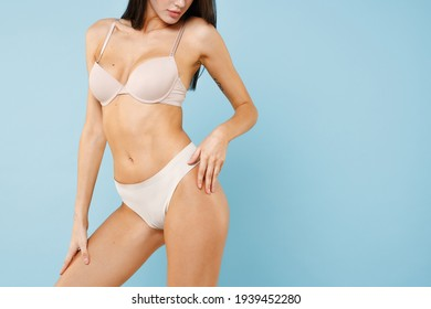 Cropped image of sexy attractive young brunette woman 20s in beige underwear showing fit body standing posing hold hand on hips legs isolated on pastel blue colour wall background studio portrait