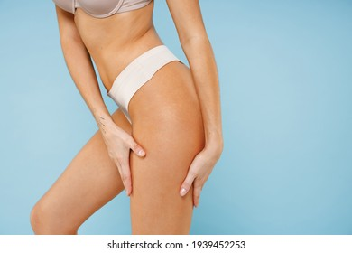 Cropped image side view young brunette woman 20s in beige casual underwear showing perfect sexy fit body standing posing hold hands on hips legs isolated on pastel blue background, studio portrait