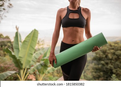 Cropped image slim woman hold in hands green rolled yoga mat on nature background