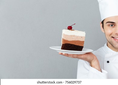 Cropped image of a smiling male chef dressed in uniform holding piece of cake on a plate isolated over gray background