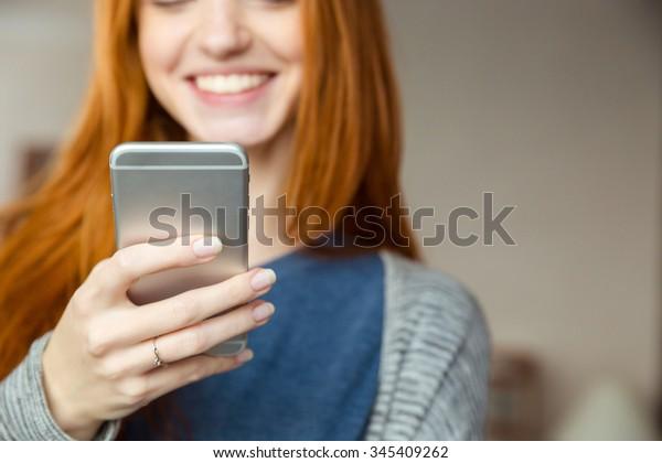 スマートフォンを使って笑顔の赤毛女性の切り抜き画像