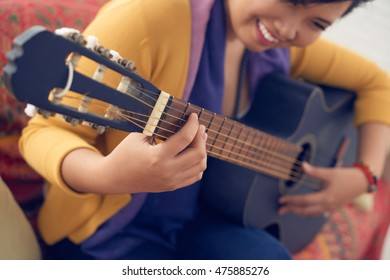 Cropped image of smiling woman playing guitar