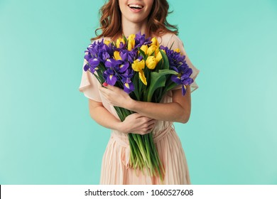 Cropped image of a smiling young girl in dress holding big bouquet of irises and tulips isolated over blue background