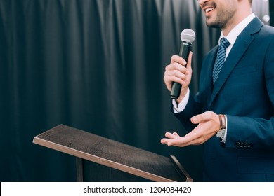 cropped image of speaker gesturing and talking into microphone at podium tribune during seminar in conference hall
