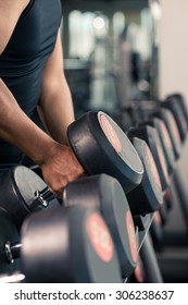 Cropped image of sportsman choosing dumbbells in the gym