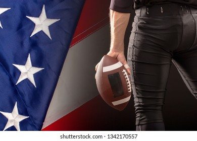 Cropped Image Of Sportsmans strong hand Holding American Football Ball with US flag on background