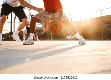Cropped image of strong multiethnic men basketball players playing basketball at the sport ground