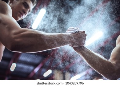 Cropped image of strong muscular men are working out in gym. Cross fit training. Using magnesium while preparing for exercise. Gymnastic chalk.