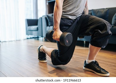 Cropped image of strong young man doing lunges with heavy dumbbells in hands when working out at home due to coronavirus pandemic