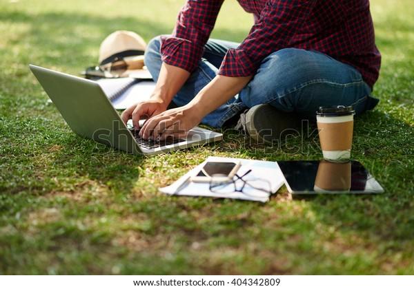 Обрезанное изображение студента, сидящего на земле и работающего на ноутбуке