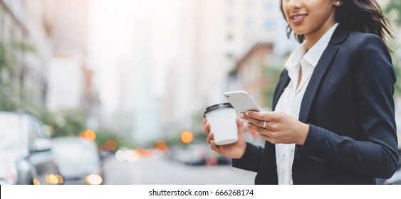 Cropped image of successful business woman wearing suit using modern smartphone and drinking coffee to go before going to work early in the morning