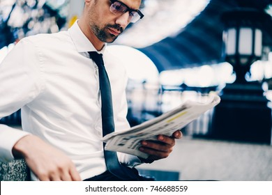 Cropped image of talented young businessman in stylish spectacles carefully reading popular finance newspaper.Close up shot of creative male entrepreneur checking information from mass-media outdoors