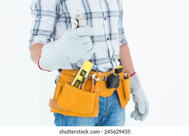 Cropped image of technician with tool belt around waist holding pliers over white background