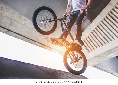 Cropped image of teenage BMX rider is performing tricks in skatepark.
