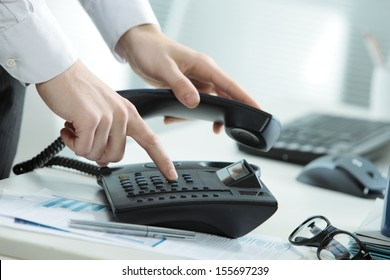 Cropped image of a telephone on a desk with a hand taking the receiver off hook