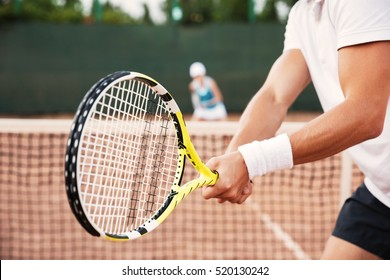 Cropped image of tennis man on court with racket