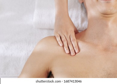 Cropped image of therapist massaging chest and shoulders of male patient