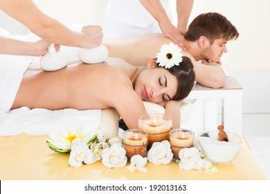 Cropped image of therapist massaging woman's back with herbal compress stamps at spa
