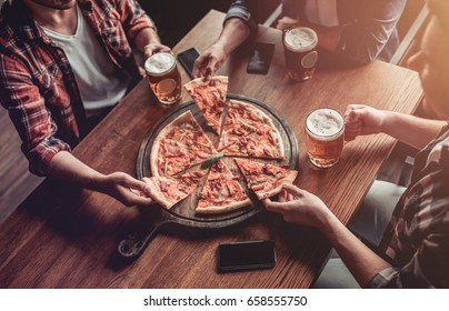 Cropped image of three male friends in bar are drinking beer and eating pizza with smartphone on the table.