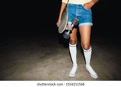 Cropped image of trendy young girl in streetwear holding skateboard at night outdoors