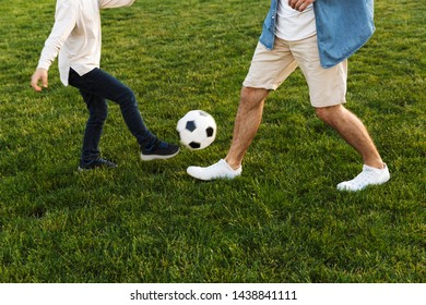 Cropped image of two brothers playing football on the lawn at the park