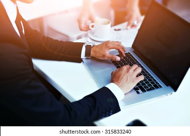 Cropped image view of man's hands in elegant suit keyboarding on laptop computer with blank copy space screen for your advertising content or text message, man working on net-book in a cafe, flare sun