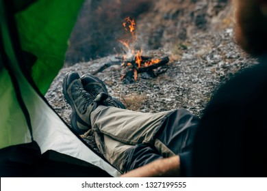 Cropped image of a view from tent entrance of young traveler man relaxing in mountains near to bonfire. Outdoor shot of male sitting in the camping tent, looking to the fire after hiking. Travel