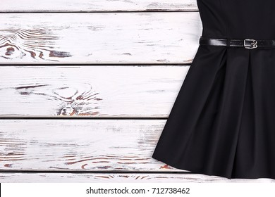 Cropped image of vintage black dress. Classical short a-line dress with belt for little girls on white wooden background, copy space. Little black retro dress.