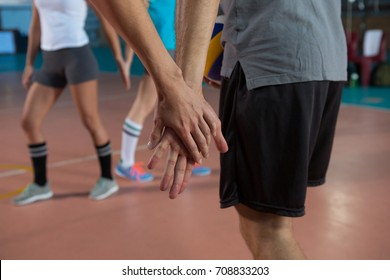 Cropped image of volleyball player holding hand with teammate at court