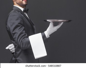 Cropped image of a waiter in black suit holding a silver tray over dark background
