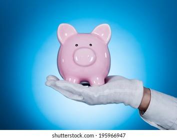 Cropped image of waiter holding piggybank over blue background