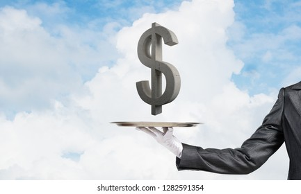 Cropped image of waiter's hand in glove presenting stone dollar symbol on metal tray with blue cloudy skyscape on background. 3D rendering.