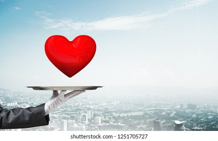 Cropped image of waitress's hand in white glove presenting big red heart on metal tray with cityscape view on background.