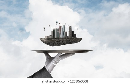 Cropped image of waitress's hand in white glove presenting modern city block on metal tray with blue cloudy skyscape on background. 3D rendering.