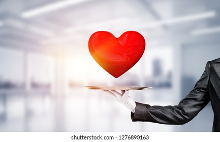 Cropped image of waitress's hand in white glove presenting big red heart on metal tray with office view on background.