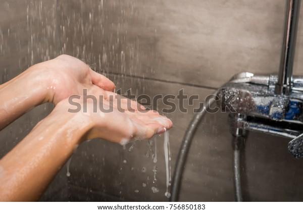 シャワーで女性の手に落ちる水滴の切り抜き画像