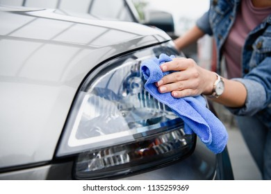 cropped image of woman cleaning car at car wash with rag