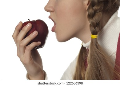 Cropped image of woman eating red apple against the white surface