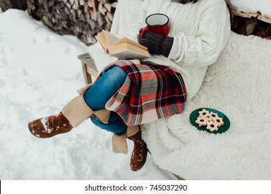Cropped image of a woman enjoying reading a book on a cold winter day. Woman relaxing on a winter day.